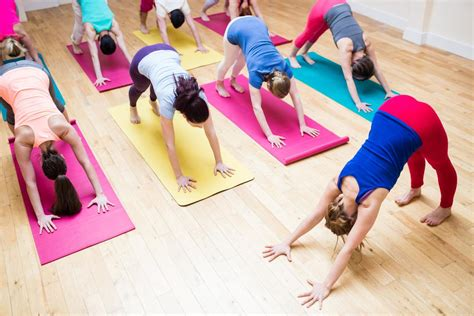 Trainer assisting group of people with downward dog yoga