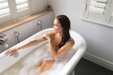 Woman taking bubble bath in bathroom at home Photo from